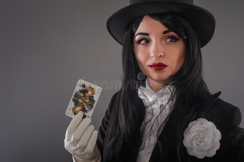 Kvinnlig trollkarl i aktördräkt med trollspöet och spelaca royaltyfri foto