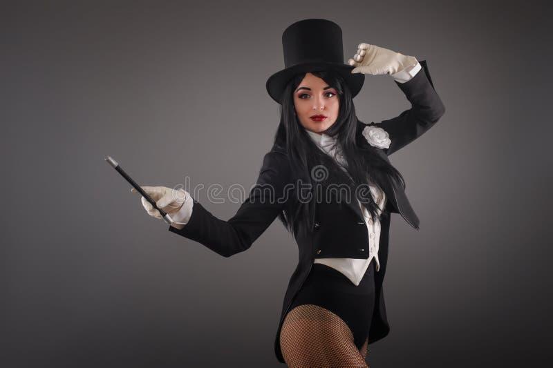 Kvinnlig trollkarl i dräktdräkt med den magiska pinnen som gör trick royaltyfri fotografi