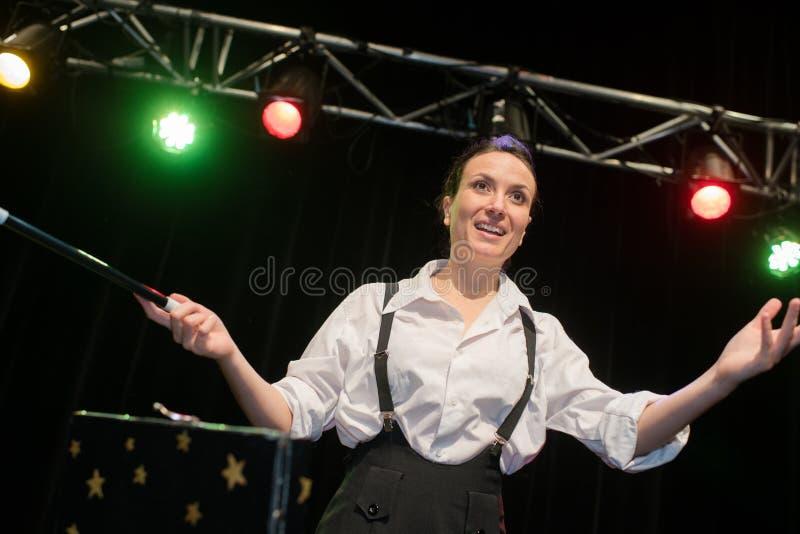 Kvinnlig trollkarl i dräktvisningtrick med trollspöet arkivfoton
