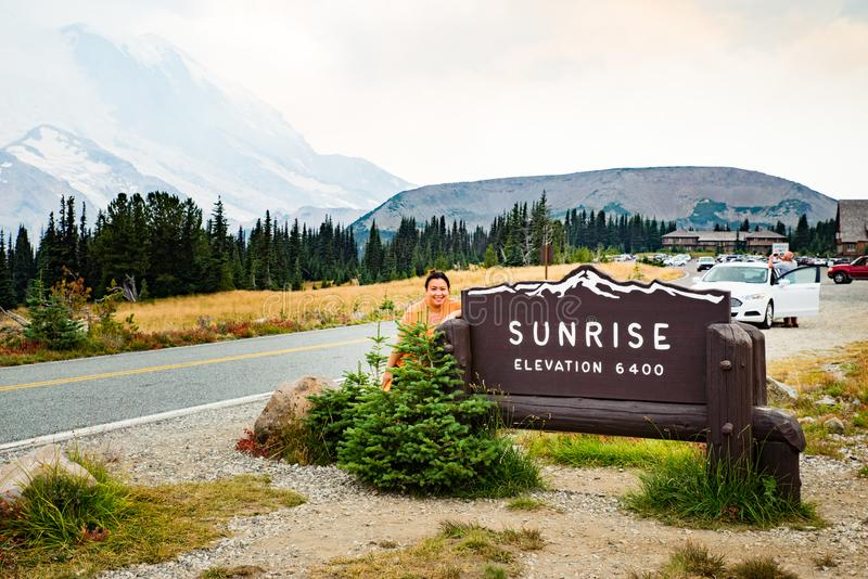 Kvinnlig turist- besöka Mt som är mer regnig på soluppgångbesökaremitten royaltyfria foton