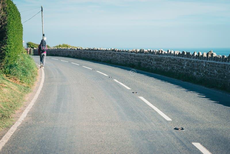 Kvinnlig turist, hichhiker, fotvandrare som går på vägen till ett D royaltyfri fotografi