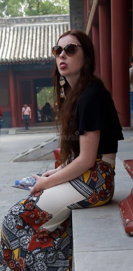 Kvinnlig turist- klibba tunga för hippie ut på kameran royaltyfri bild