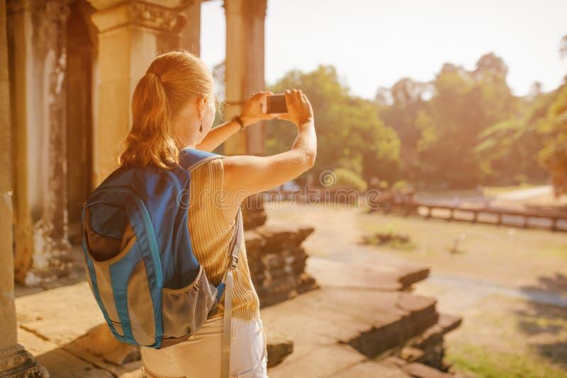 Kvinnlig turist med smartphonen som tar bilden av Angkor Wat royaltyfria foton