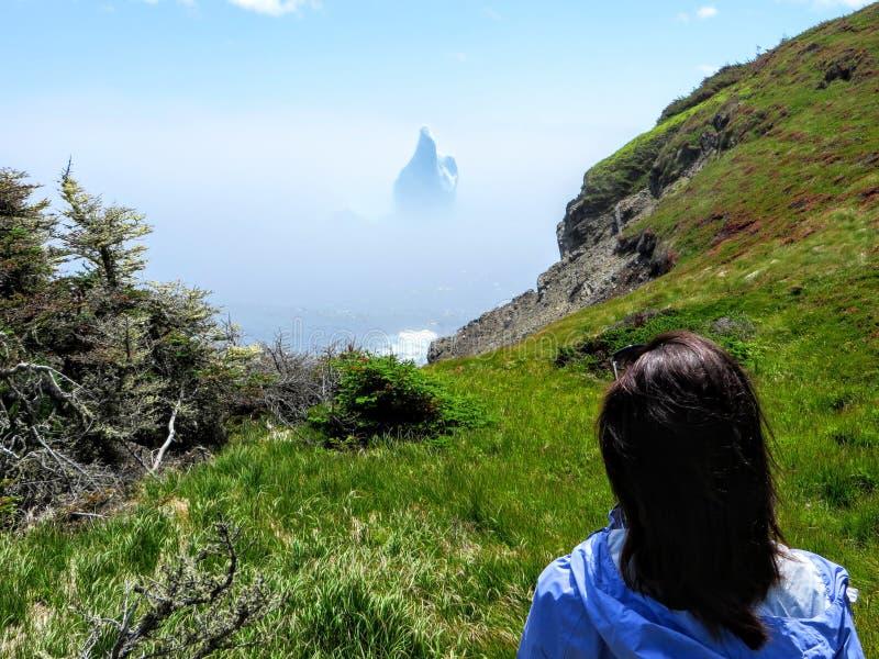 Kvinnlig turist som beundrar ett oerhört isberg som svävar längs den ojämna kusten bredvid den Skerwink slingan i Newfoundland oc royaltyfria foton