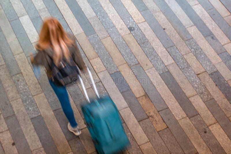 Kvinnlig turist som går med hennes resväska arkivfoto
