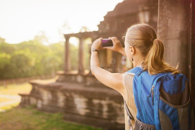 Kvinnlig turist som tar bilden av Angkoret Wat i Cambodja arkivbild