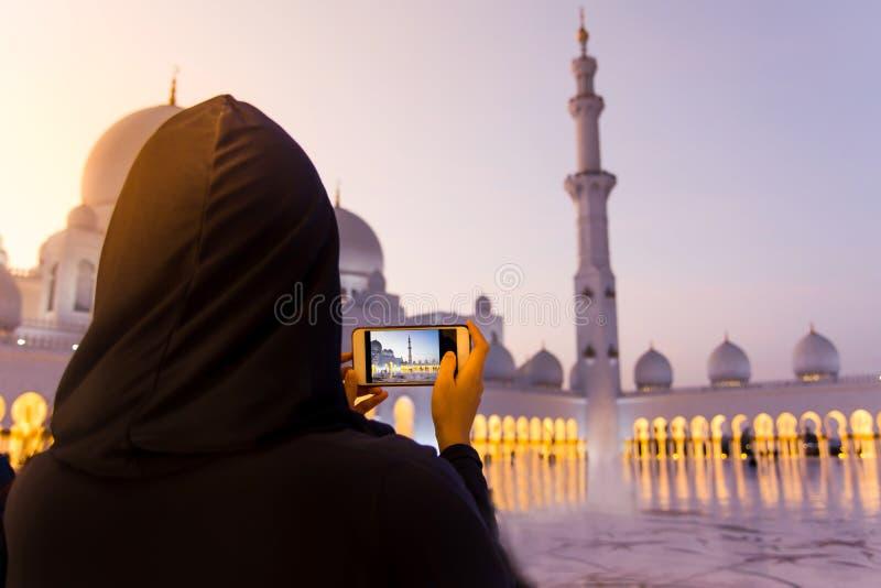 Kvinnlig turist som tar bilden av Sheikh Zayed Grand Mosque royaltyfri fotografi