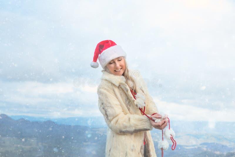 Kvinnlig tyckande om jul för en vinter i blåa berg arkivbild