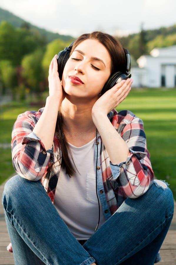 Kvinnlig tyckande om musik för fridsam hipster utanför i parkera arkivbilder