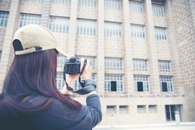 Kvinnlig ung handelsresande med ryggsäck- och fotokameran i den gamla staden arkivfoton
