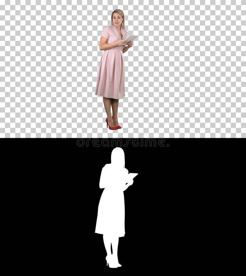 Kvinnlig ung kvinna i rosa anseende med minnestavlan och ge siganförande till kameran, Alpha Channel royaltyfri foto
