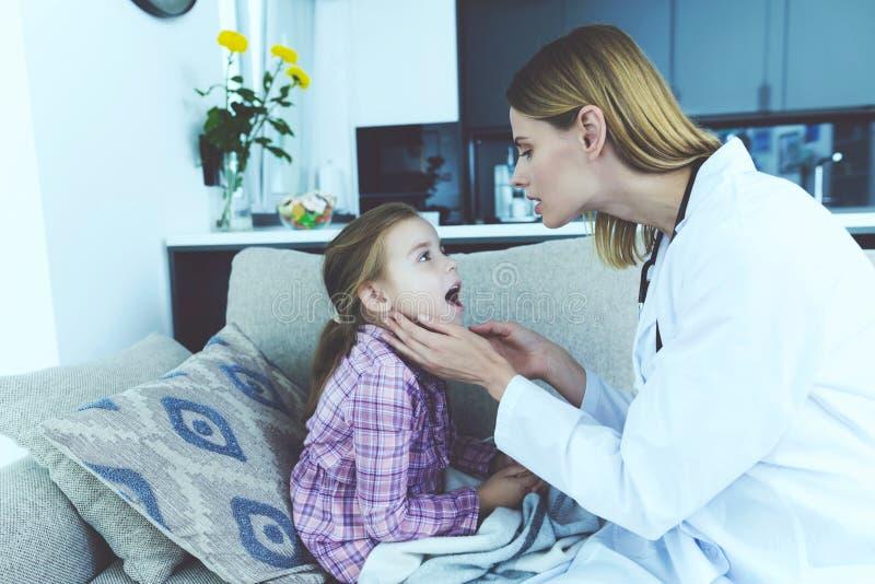Kvinnlig unge för doktor Examines Pretty Sick hemma royaltyfria bilder