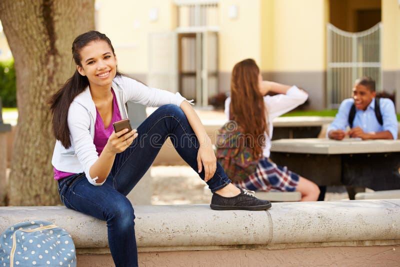 Kvinnlig universitetsområde för högstadiumstudentUsing Phone On skola arkivfoton
