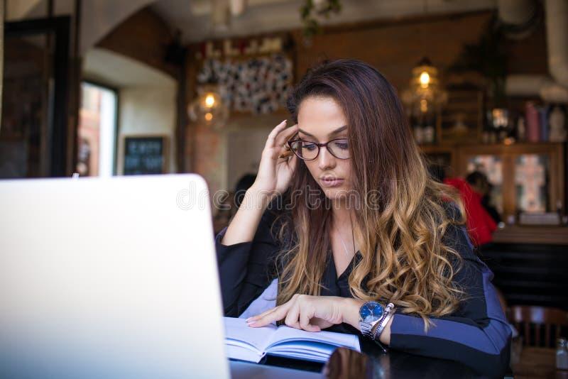 Kvinnlig universitetsstudent som bär i stilfulla exponeringsglas som lär med notepaden och netto-boken royaltyfri fotografi