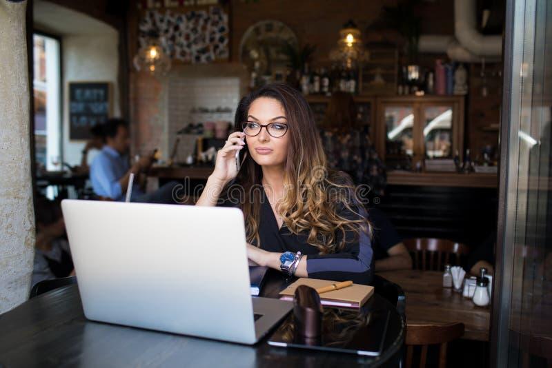 Kvinnlig universitetsstudent som kallar via mobiltelefonen, medan sitta med netbook i restaurang arkivbilder