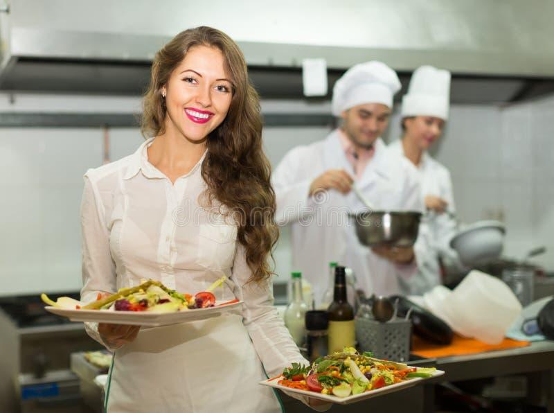 Kvinnlig uppassare som tar maträtten på kök royaltyfri fotografi