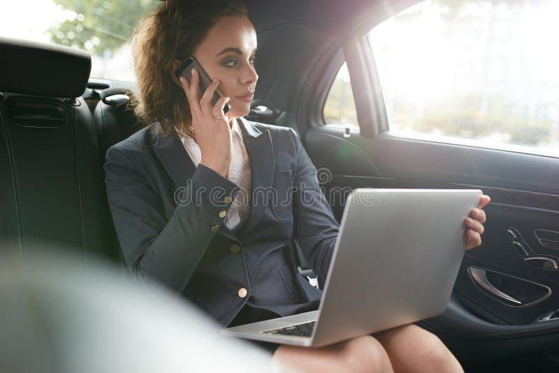 Kvinnlig utövande resande som arbetar i lyxig bil arkivfoton