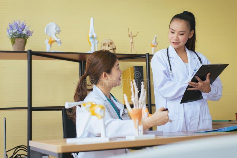 Kvinnlig utbildning för härlig asiatisk medicinare och använda den skelett- handmodellen på sjukhuset tillsammans royaltyfri fotografi