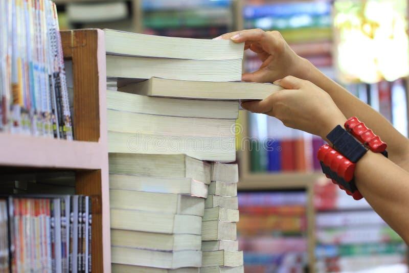 Kvinnlig väljande bok för hand från bokhyllan i arkivrummet arkivfoton
