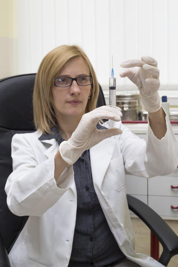 Kvinnlig vaccinering för doktor Preparing Syringe For i klinik fotografering för bildbyråer
