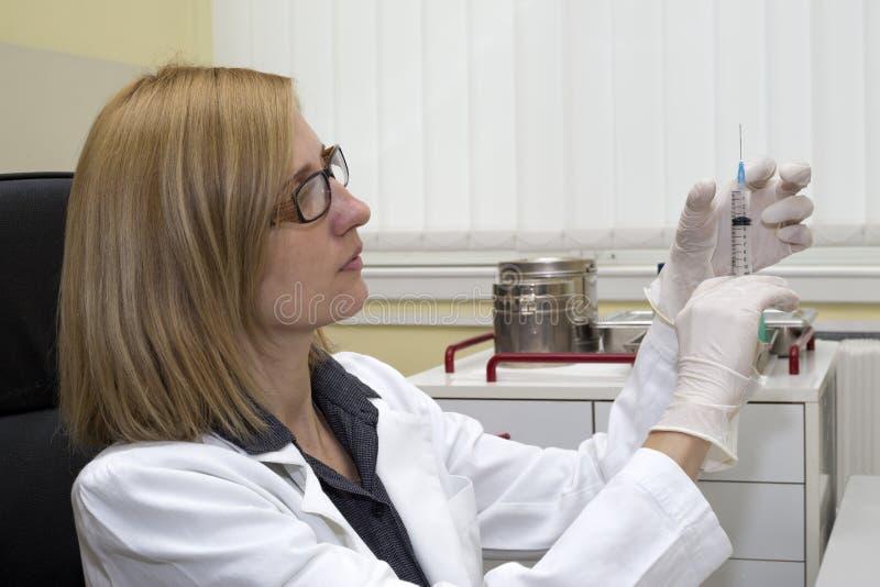 Kvinnlig vaccinering för doktor Preparing Syringe For i klinik arkivbilder