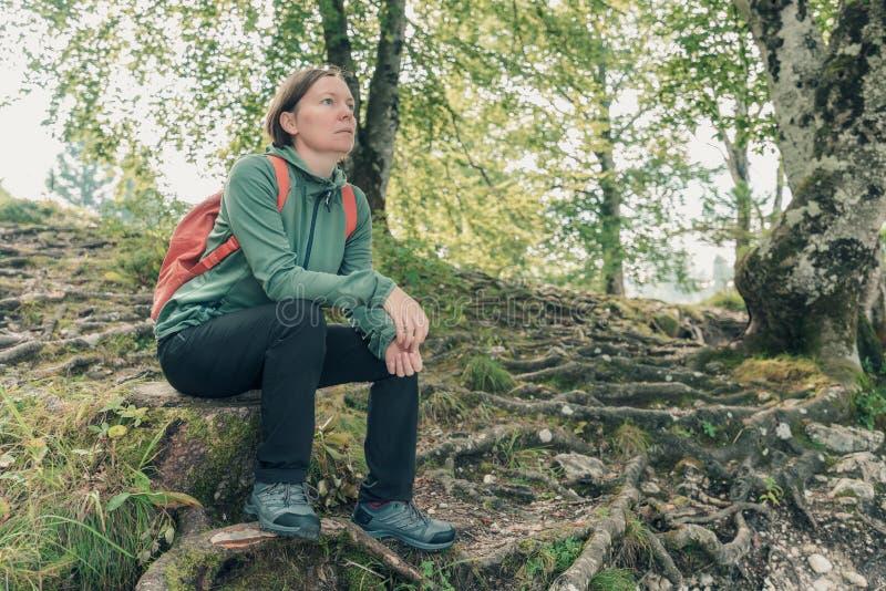 Kvinnlig vandrare som vilar och överväger i skog royaltyfri foto