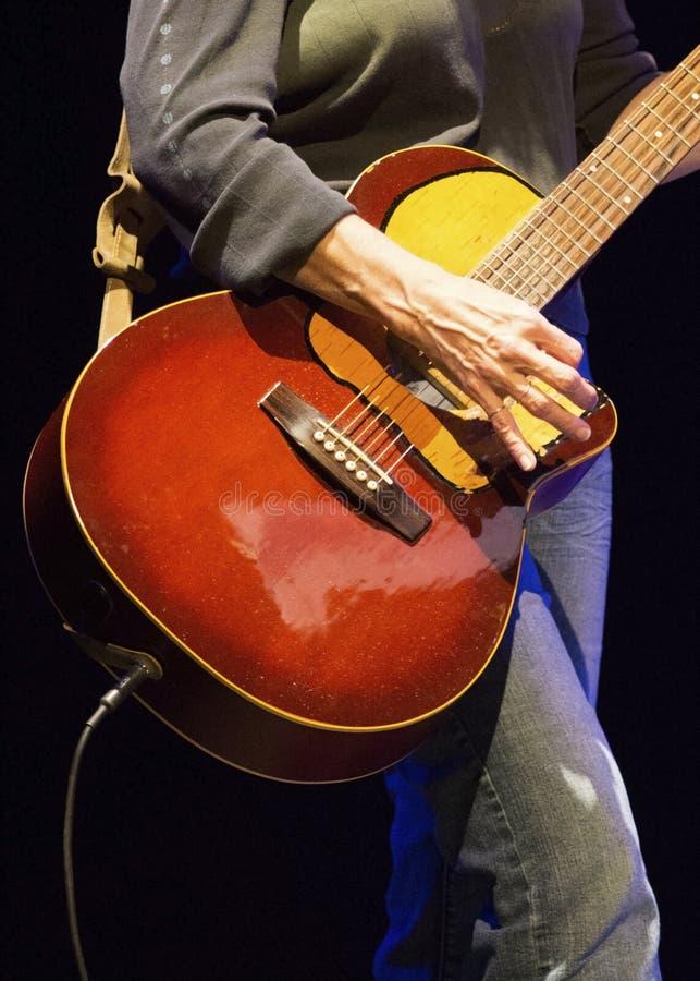 Kvinnlig vippa som spelar den röda gitarren arkivbilder