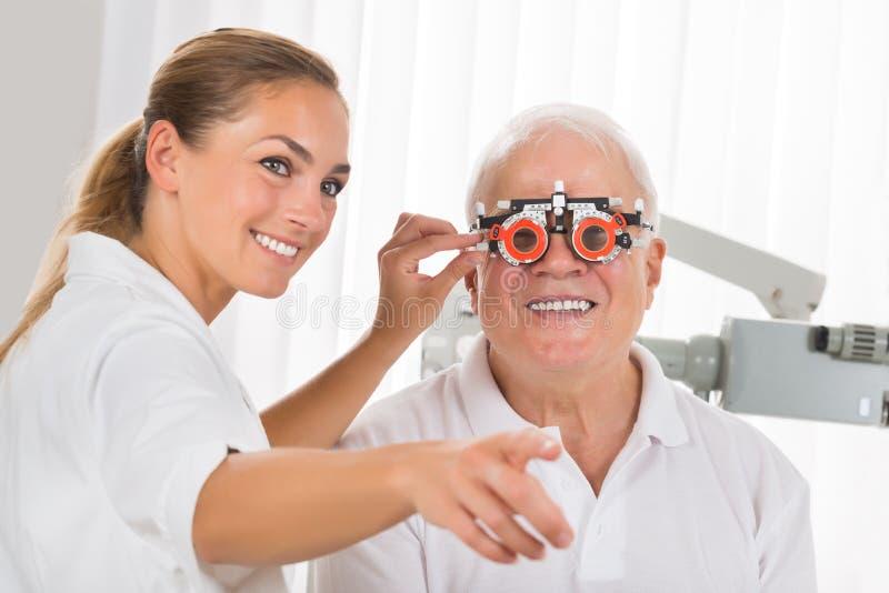 Kvinnlig vision för optometrikerChecking Patient ` s med försökramen fotografering för bildbyråer