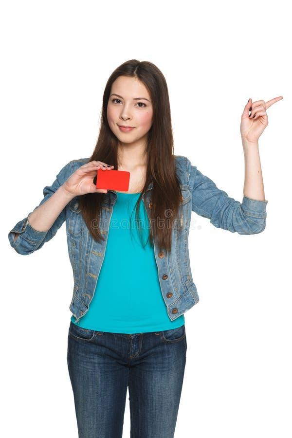Kvinnlig visningmellanrumskreditkort och peka till sidan arkivfoto