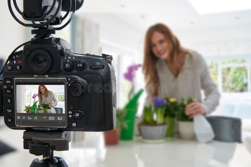 Kvinnlig Vlogger som gör den sociala massmediavideoen om Houseplantomsorg för internet royaltyfri foto