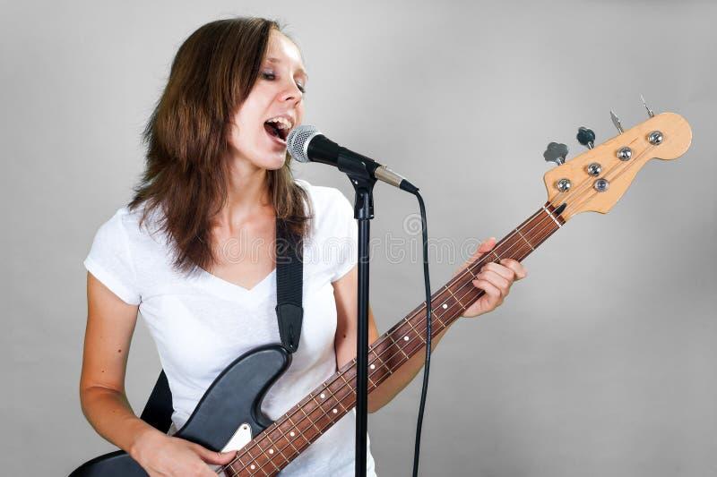 Kvinnlig vokalist med mikrofonen och elbasen på grå färger royaltyfri foto