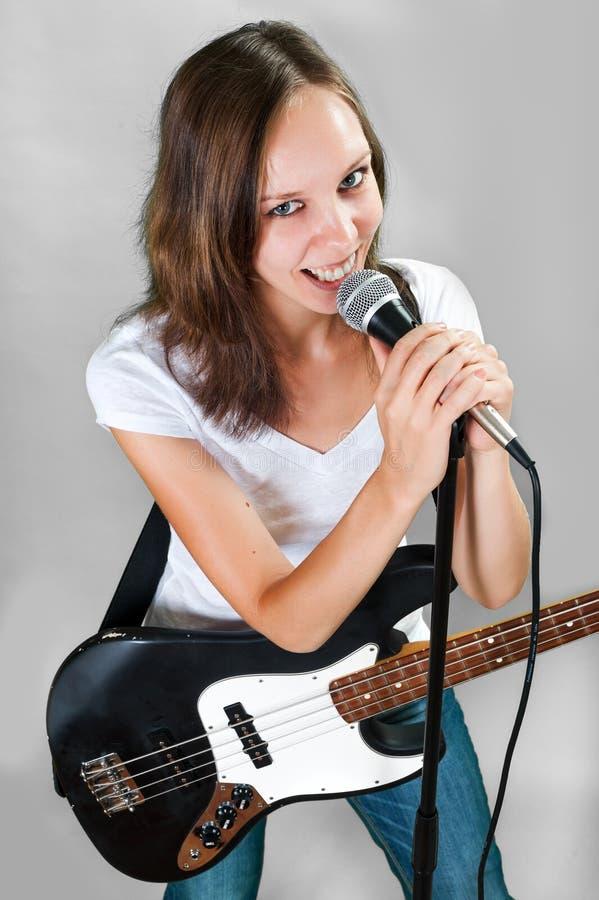 Kvinnlig vokalist med mikrofonen och elbasen på grå färger fotografering för bildbyråer