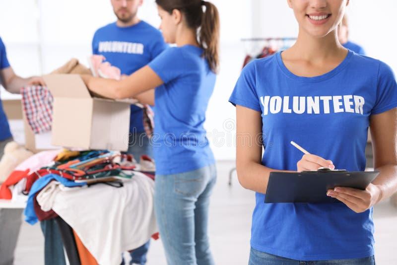 Kvinnlig volontär med skrivplattaförteckningsdonationer royaltyfria foton