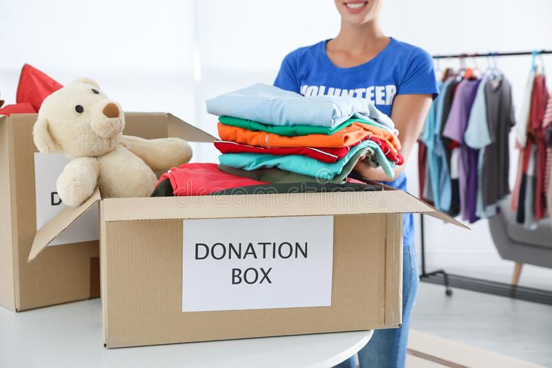 Kvinnlig volontär som inomhus samlar donationer på tabellen royaltyfria bilder