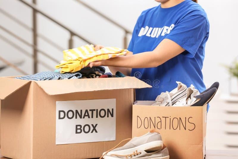 Kvinnlig volontär som sätter kläder i donationask royaltyfria bilder