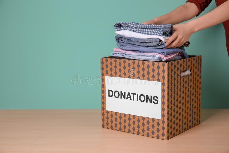 Kvinnlig volontär som sätter kläder in i donationasken royaltyfri bild