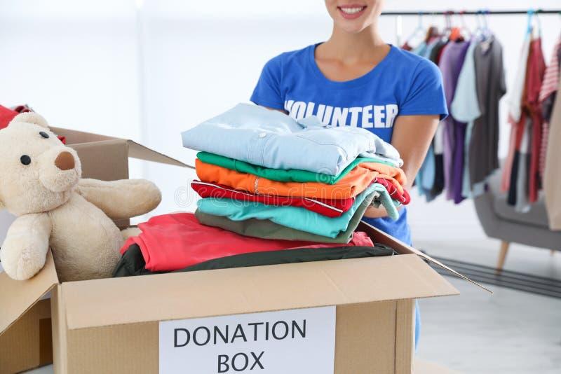 Kvinnlig volontär som sätter kläder in i donationasken fotografering för bildbyråer