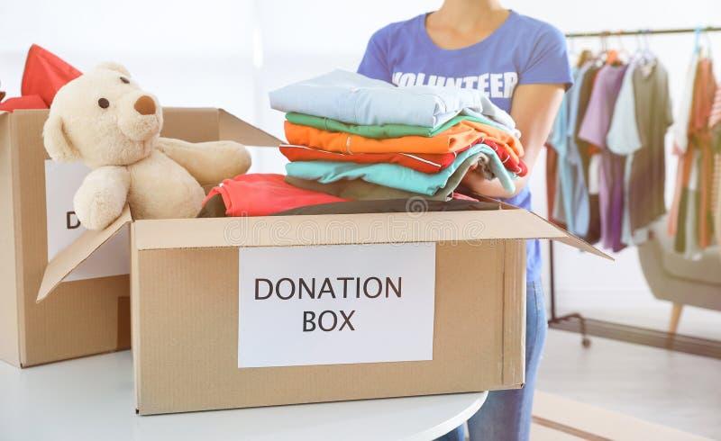 Kvinnlig volontär som samlar donationer på tabellen royaltyfria foton