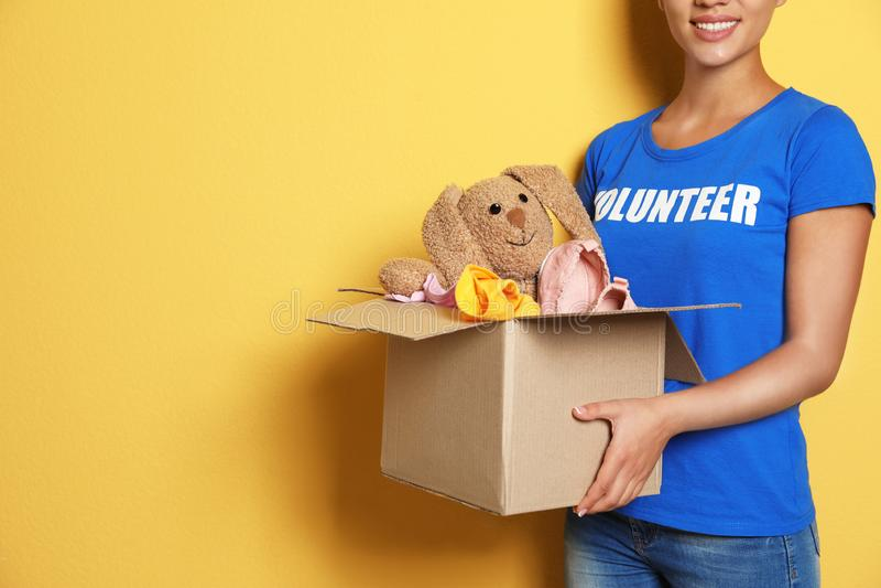 Kvinnlig volontärinnehavask med donationer på färgbakgrund royaltyfri foto