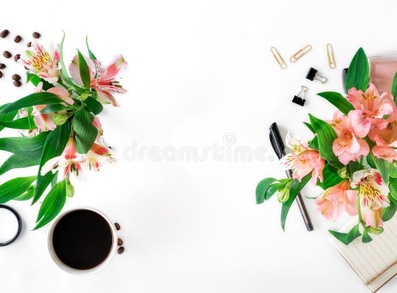 Kvinnlig workspace med den kontorstillbehör, kaffe och buketten av arkivfoton
