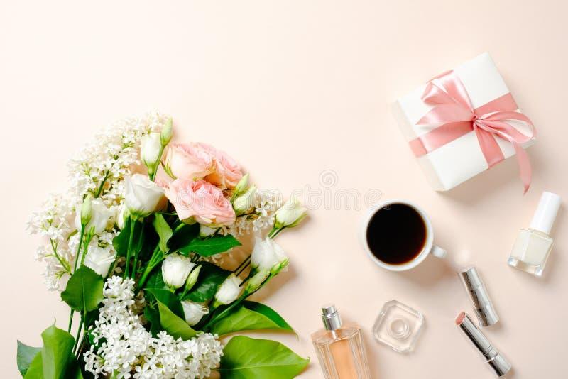 Kvinnlig workspace med rosblommabuketten, kvinnlig tillbehör, skönhetsmedel, gåvaask F?r kvinna` s f?r l?genhet lekmanna- skrivbo royaltyfri fotografi