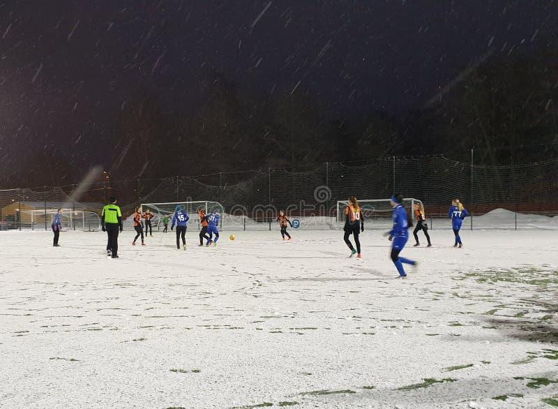 Kvinnlig yngre fotbollsmatch i vinter på det dolda fältet för snö - Helsingfors, Finland arkivbild