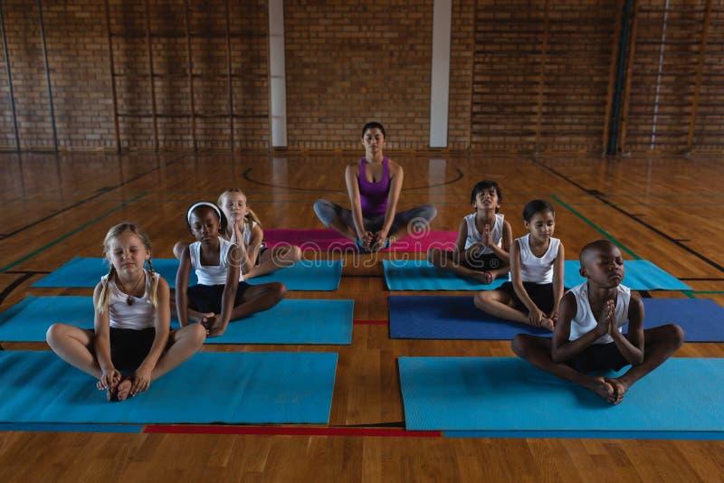 Kvinnlig yogalärare och skolbarn som gör yoga och mediterar på en yoga som är matt i skola fotografering för bildbyråer