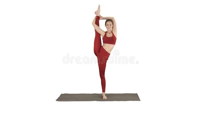 Kvinnlig yogamodell Making Standing Split som ler på vit bakgrund arkivbilder