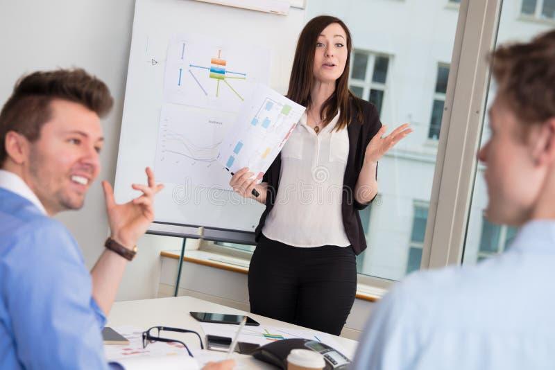 Kvinnlig yrkesmässig geende presentation till manliga kollegor arkivfoton