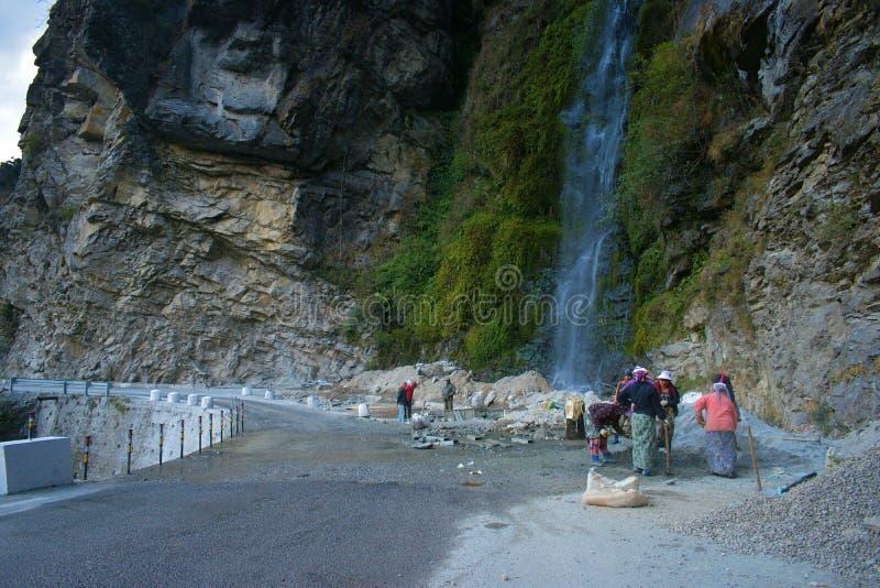 Kvinnliga arbetare som gör bergvägreparation och byggnationer i Himalayan berg, nära Thimphu, Bhutan arkivbild