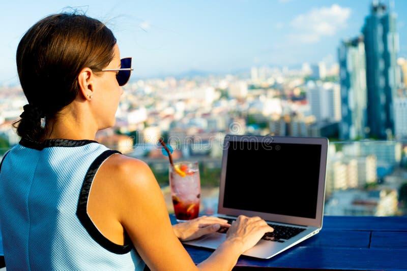 Kvinnliga arbeten på en bärbar dator i ett kafé på taket av ett höghus med en härlig panoramautsikt av staden, slut upp royaltyfria bilder