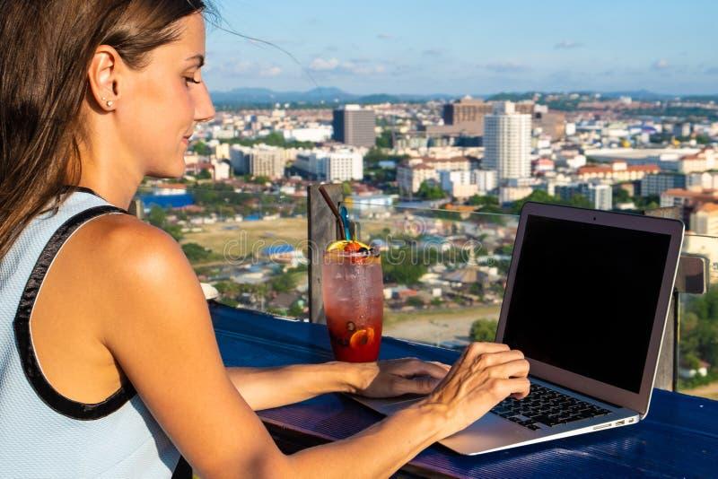 Kvinnliga arbeten på en bärbar dator i ett kafé på taket av ett höghus med en härlig panoramautsikt av staden, slut upp arkivfoto