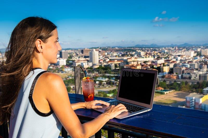 Kvinnliga arbeten på en bärbar dator i ett kafé på taket av ett höghus med en härlig panoramautsikt av staden, slut upp arkivfoton