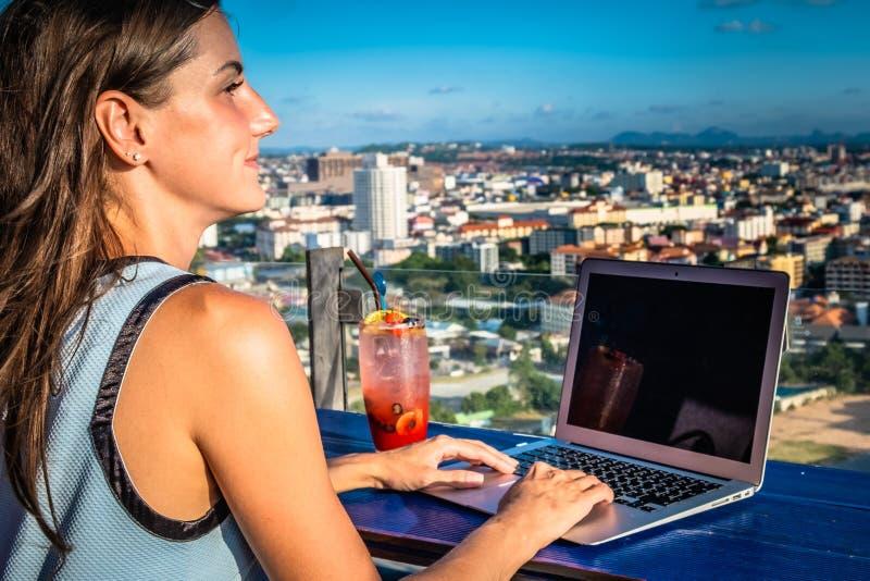 Kvinnliga arbeten på en bärbar dator i ett kafé på taket av ett höghus med en härlig panoramautsikt av staden, slut upp arkivbild